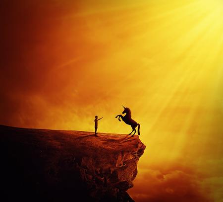 野生のユニコーンを飼いならすしようとして崖の割れ目の端に立っている男の子とのどかな景色。新しい友情、大胆不敵な記号の始まり