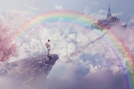 Fantasy world imaginary view. Young boy looking at the path to a castle above clouds. Life journey below a rainbow in paradise.