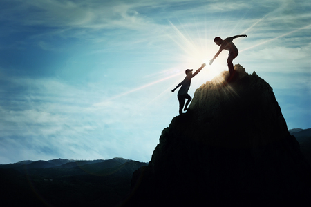 Sylwetka Pomocna dłoń między dwoma chłopcami wspinaczka skalistym niebezpiecznego urwiska. Przyjazne strony na wysokiej górze wędrówki. Inspirująca pracy zespołowej, Symbol wiary i wsparcia.