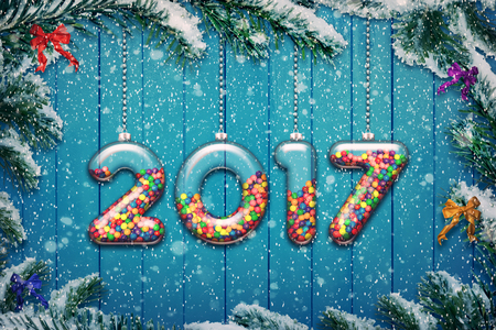 Set of transparent glass with multicolored candy and sweets hang on a snowy Christmas tree branch. New year 2017 background.