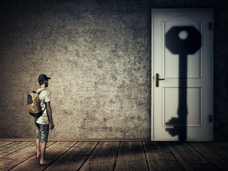 Silhouette of a man casting a key shape shadow on a room door. Conceptual image symbolizing the magical transformation as human is the key to all closed doors. Human adaptation to difficult conditions and all the intellectual labyrinths.