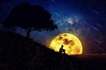 Boy sit alone on a hill in the center of nature, over a full moon night background. Standing away from the crowd, waiting for the healing power of the nature.