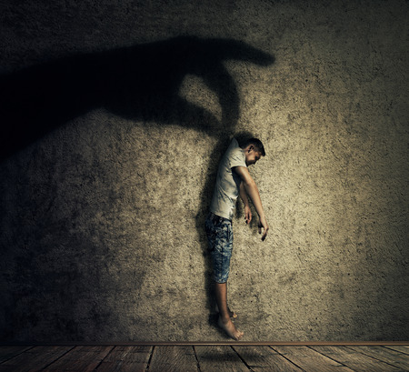 manipulate: Human hand shadow holding a powerless man hanging. Conceptual image symbolizing manipulation, business control as a marionette.