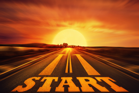 long way: Word Start written on an asphalt road and two arrows as motivation. Long way ahead as a concept of start straight for business.