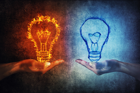 Two human hands holding flaming and splashing light bulbs on a gray background. Thinking exchange and idea partnership business concept. Fire against water symbol.