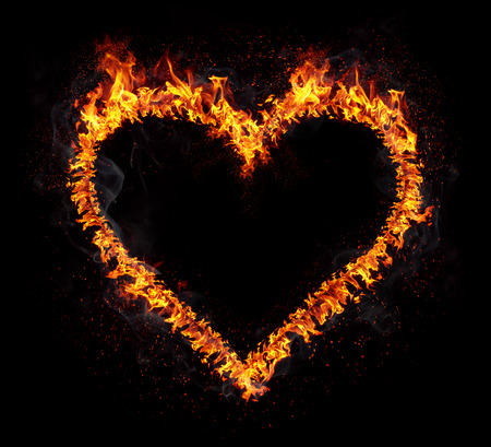Flaming heart isolated on black background. Love symbol.