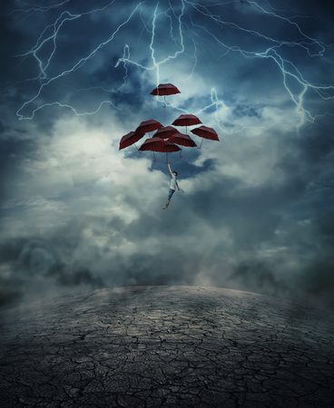 trouble free: Young man with a lot of umbrellas as an air balloon rise up to the sky full of lightnings, above the cracked desert ground. Risk and success concept. Stock Photo