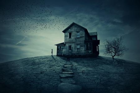 遠く離れた誰かを探して、荒廃した家のコーナーに若い男が立っています。幽霊、乾燥した土地とツリーの荒廃の家。