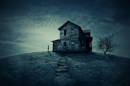 Young man stand at the corner of a ravaged house, looking far away for someone. A ghost, desolated house with a dry land and tree. Stockfoto