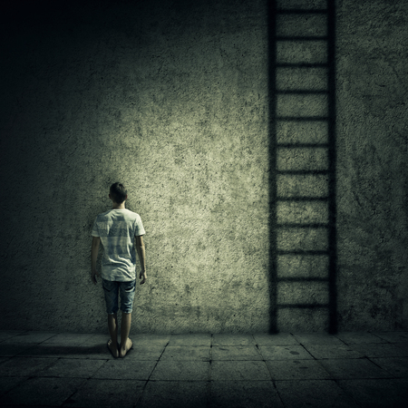 figuring: Abstract idea with a person standing in a dark room, in front of a concrete wall, figuring a ladder to escape. Surrounded by limitations, daily routine.