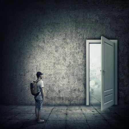暗い部屋、開いたドアの前に立っている人の抽象的なアイデア。機会、別の世界への入り口をエスケープします。
