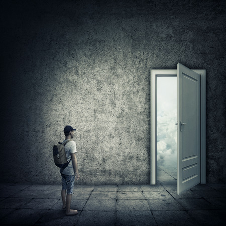 Abstract idea with a person standing in a dark room, in front of a opened door. Escape opportunity, entrance to another world.