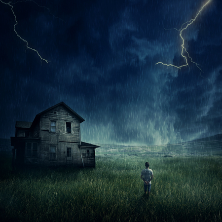 ravage: Spooky landscape as a young boy walking in the meadow look at a ghost, haunted house below a dark stormy sky.