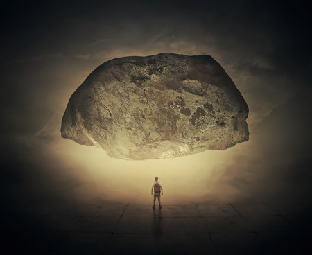 difficult lives: Surrealistic image as a man, with a bag in his back, stand in a foggy street below a huge squeezing rock. Life pressure and stress concept.