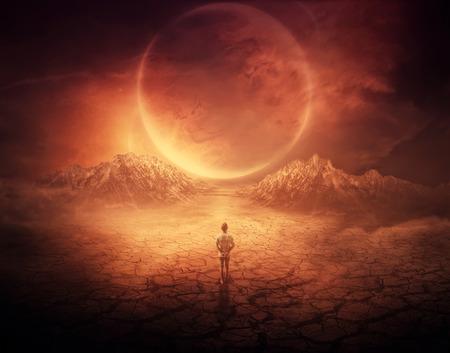 若い男の子としてシュールな背景は、乾燥してひび割れている地面、空に輝くスペース オブジェクトを次の別の惑星に歩きます。
