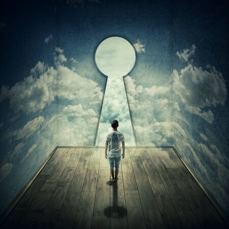 Abstract idea with a person standing in front of a big keyhole doorway surrounded by limitations daily routine concrete walls with clouds texture, casting a key shadow. Stock Photo