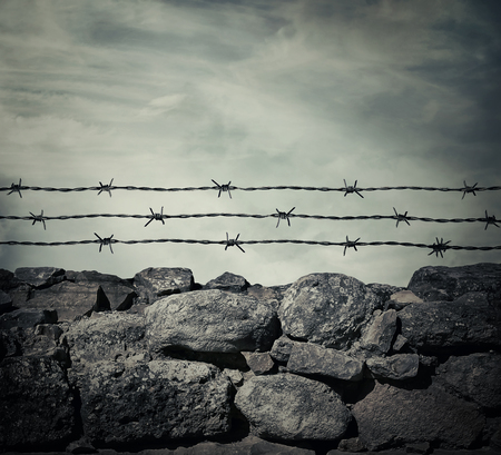 Masonry stone wall fence of a prison with barbed metallic wire above. Фото со стока
