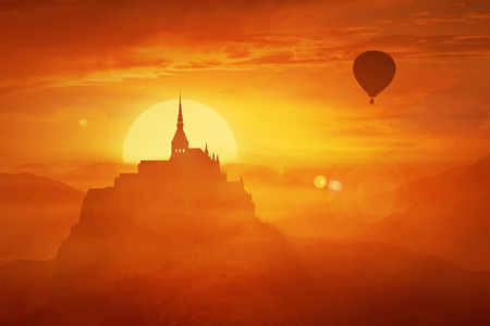 Beautiful sunset landscape over the misty kingdom between the orange hills in the center of nature and the silhouette of a flying air balloon. Fantasy world imaginary view, another reality concept. Stock Photo