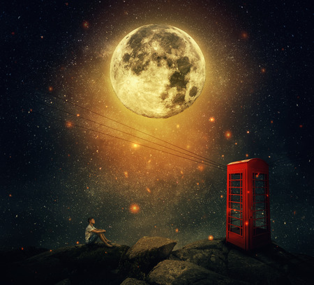 Imaginary view as a young man sitting on the cliff, wait for someone to call him at the phone booth (box). Full moon night with a starry sky background. Loyalty and hard determination concept. Stock Photo