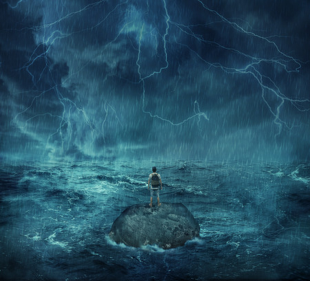 Lost man standing abandoned on a rock island in middle of the ocean, in a stormy night with lightnings in the sky. Looking for help, trying to survive. Adventure, journey and hard determination concept. Stock Photo