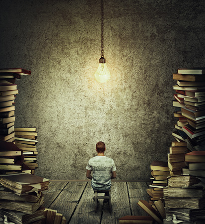 Creative idea concept as a person, scribe sitting in a dark room surrounded by tall piles of books and a suspended glowing lightbulb above his head. Wise librarian or writer get inspiration.