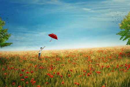 Young boy stand on a country meadow with million of red poppies, trying to catch his red umbrella that fly to the sky. The pursuit of happiness and success concept. Life joy, fun and happiness.