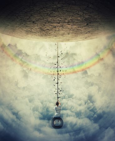Young boy suspend on a tire swing in the clouds over the rainbow, avoiding the gravitational force. Having fun and freedom concept.