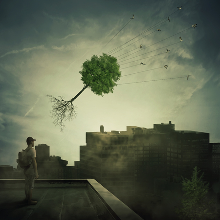 Surreal view as a boy stand on the rooftop looking at a flock of birds carrying a tree pulled from roots, flying over the polluted, foggy city. Town conservation and greening concept.