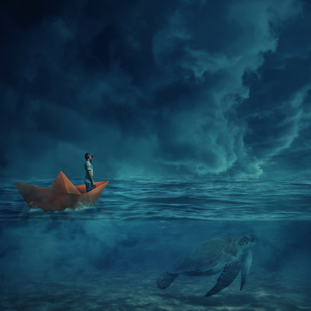 Young boy in a orange paper boat sail lost in the ocean, in a stormy night and a huge turtle underwater, as a guide, show him the way home. Adventure and journey concept. Stock Photo