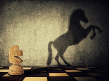 Magical transformation as a wooden knight chess piece casting a shadow of a wild horse on two legs on the wall. Symbol of business aspirations, freedom and leadership concept. Stock Photo