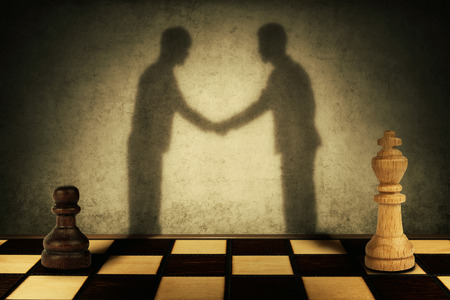 Chess pawn and king standing in front one another with their shadow transform into businessman giving handshake. Business hierarchy levels peace concept.
