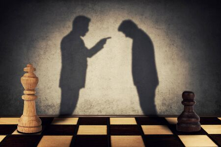 Chess pawn and king standing in front one another with their shadow transform into businessman silhouettes. Business hierarchy misunderstanding concept. Stock Photo