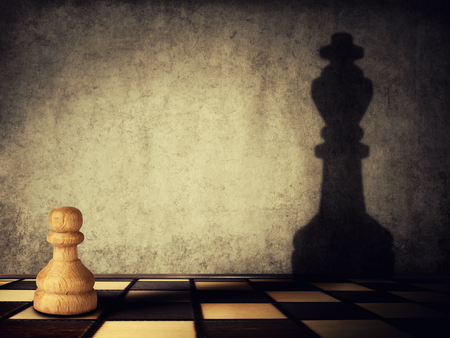 Pawn chess piece casting a shadow of a king on a concrete wall. Business aspirations and leadership concept. Magical transformation