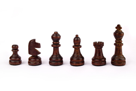 A set of standard, wooden black chess pieces isolated on white background