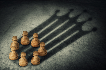 Chess pawn standing together, arranged in a circle joining the power, casting a crown shaped shadow. Business group leadership and team working concept. Belief in success. Stock Photo