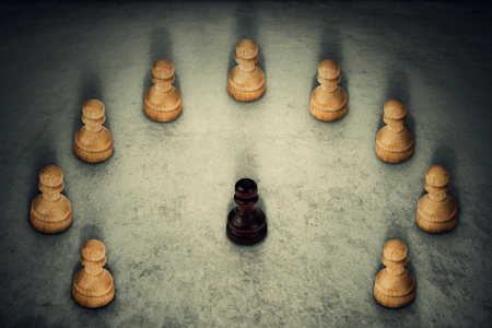 Black chess pawn piece surrounded by white ones joining their power together. Business group leadership and team working symbol. Racism or bullying concept