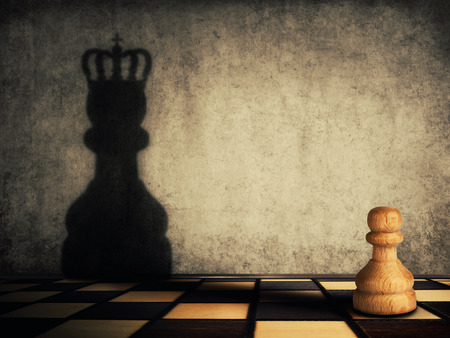 Pawn chess piece glorification, casting a shadow of coronation on a concrete wall. Business aspirations and leadership concept. Magical transformation, become a king.