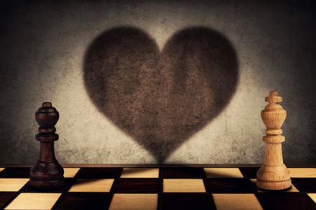 Black queen and white king chess pieces standing in front one another casting their shadows transform into a big heart on the wall. Love symbol, impossible relationship, togetherness concept.