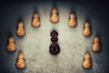 Black queen chess piece surrounded by white pawns joining their power together. Business group leadership and team working symbol.