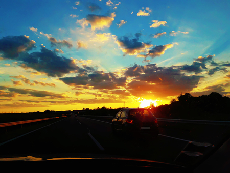 The unforgettable journey with a car on a Hungarian highway road meeting a magnificent sunset.