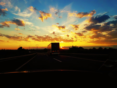 Driving on a highway behind a truck over a beautiful sunset background. Car travel, holiday journey.