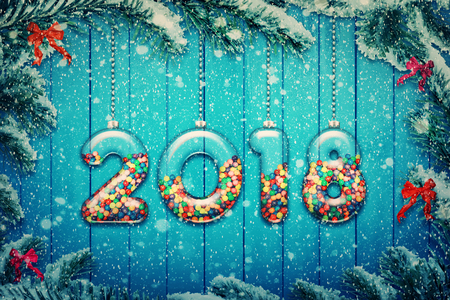 Happy new year 2018 background! Set of transparent glass with multicolored candy and sweets hang on a snowy Christmas tree branch. Stock Photo