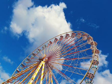 Close up view of the Roue de Paris, the big ferris wheel above a deep blue sky background located in the Jardin des Tuileries in Paris, France.
