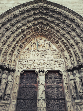 Sculpted tympanum of the Last Judgment over the gate of the Notre-Dame de Paris, France.