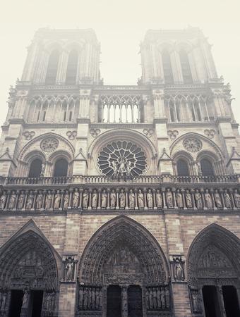 Facade of Notre Dame de Paris cathedral in a foggy morning.