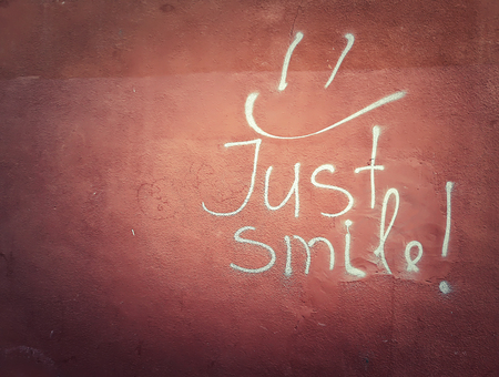 Just smile writting on a red wall, white graffiti smiley face symbol on concrete texture. Stock Photo