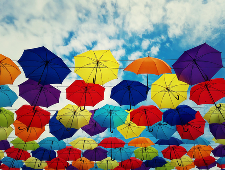 Colorful umbrellas hanging above a city street isolated on blue sky background. Bright urban decoration.