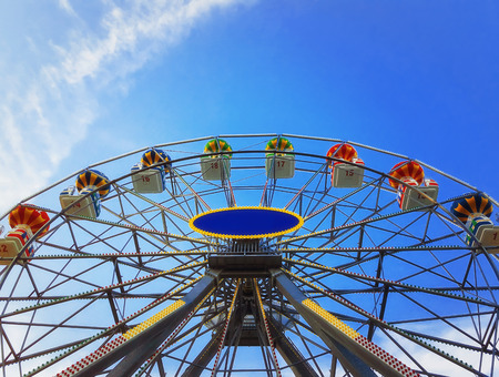 Close up view of a big ferris wheel above a deep blue sky background.