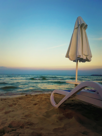Beautiful sunset view as a deckchair with umbrella on the sand beach in front of a blue sea water.