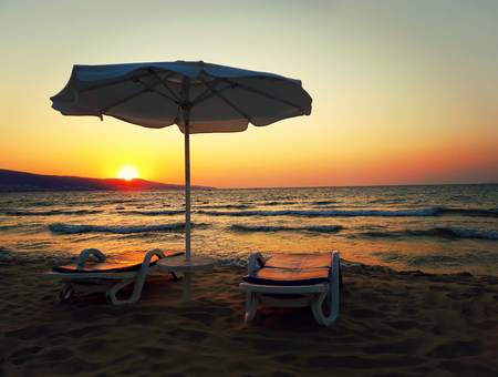 Romantic scene as a sunset at the sea shore with two sunbeds and an umbrella on the sand beach in front of the sun rays.